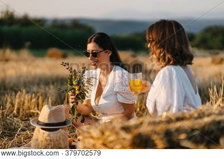 Best Friends Enjoying Their Time Together On A Picnic. One Is Drinking Orange Juice And The Other Is