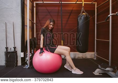 Portrait Of Sporty Young Asian Woman In Gym Clothing Doing Core Exercises With An Exercise Ball Whil