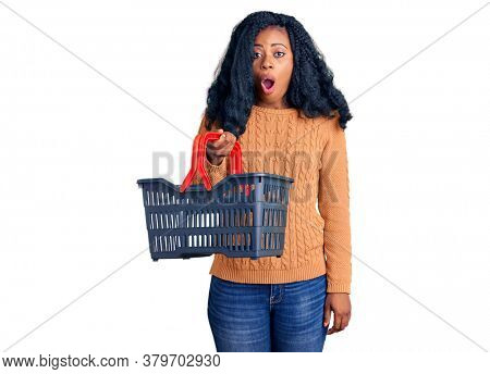 Beautiful african american woman holding supermarket shopping basket scared and amazed with open mouth for surprise, disbelief face