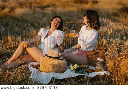 Two girlfriends lying on a picnic blanket and smiling. Enjoying time in nature. Leisure and free time