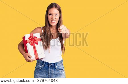 Young beautiful hispanic woman holding gift annoyed and frustrated shouting with anger, yelling crazy with anger and hand raised