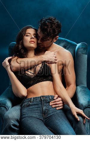 Shirtless Man Embracing Girlfriend In Bra And Jeans On Armchair On Black With Smoke