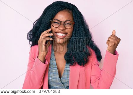 Beautiful african woman having conversation talking on the smartphone screaming proud, celebrating victory and success very excited with raised arm