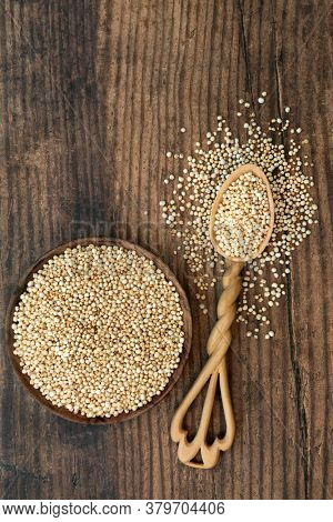 Puffed quinoa grain health food in a bowl and lovespoon. Highly nutritious rich in fibre, antioxidants, protein, with a low GI for blood sugar control for diabetics. Flat lay on rustic wood.