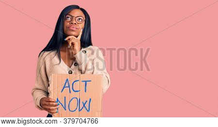 Young african american woman holding act now banner serious face thinking about question with hand on chin, thoughtful about confusing idea