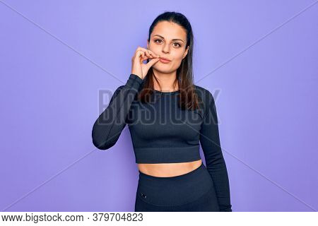 Young beautiful brunette sporty woman wearing casual sportswear over purple background mouth and lips shut as zip with fingers. Secret and silent, taboo talking