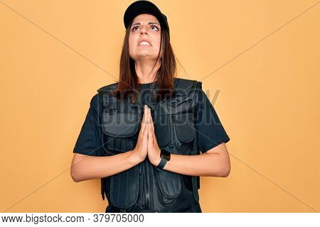 Young beautiful brunette policewoman wearing police uniform bulletproof and cap begging and praying with hands together with hope expression on face very emotional and worried. Begging.