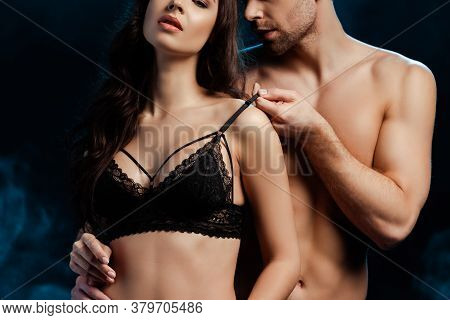 Cropped View Of Muscular Man Touching Bra Of Sexy Woman On Black With Smoke