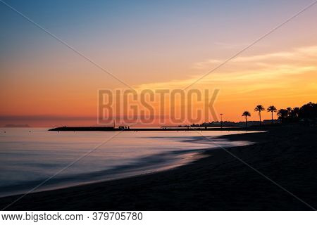 Sunset At A Beach In The Costa Del Sol In Marbella, Spain, With The Silhouette Of A Pier And Gibralt