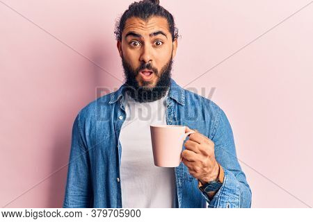 Young arab man holding coffee scared and amazed with open mouth for surprise, disbelief face