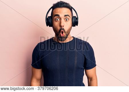 Young hispanic man listening to music using headphones scared and amazed with open mouth for surprise, disbelief face