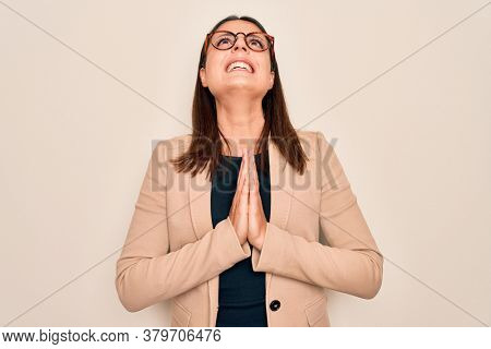 Young beautiful brunette businesswoman wearing jacket and glasses over white background begging and praying with hands together with hope expression on face very emotional and worried. Begging.