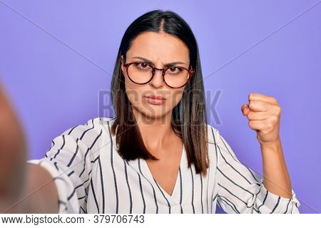 Young beautiful brunette woman wearing striped shirt and glasses making selfie by camera annoyed and frustrated shouting with anger, yelling crazy with anger and hand raised