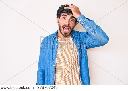 Handsome young man with curly hair and bear wearing casual denim jacket surprised with hand on head for mistake, remember error. forgot, bad memory concept.