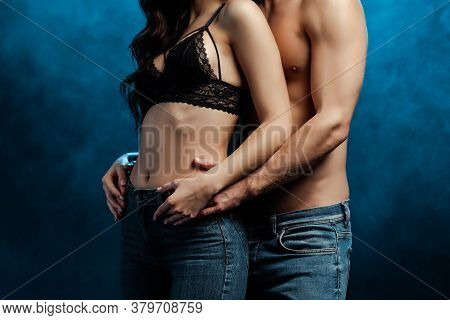 Cropped View Of Shirtless Man Hugging Girlfriend In Bra And Jeans On Black With Smoke