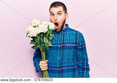 Young handsome man holding bouquet of flowers scared and amazed with open mouth for surprise, disbelief face