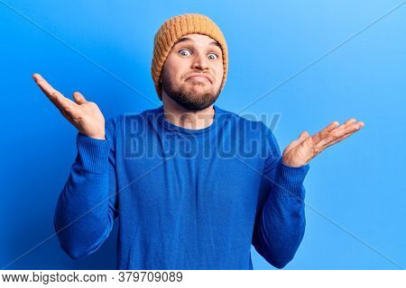 Young handsome man wearing casual sweater and wool cap clueless and confused with open arms, no idea and doubtful face.