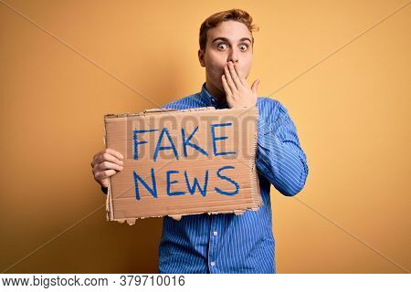 Young handsome redhead man holding banner with fake news message over yellow background covering mouth with hand, shocked and afraid for mistake. Surprised expression