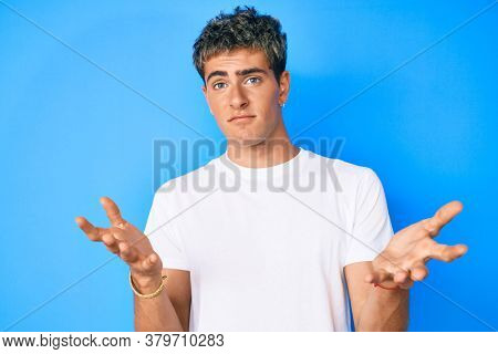Young handsome man wearing casual white t shirt clueless and confused expression with arms and hands raised. doubt concept.