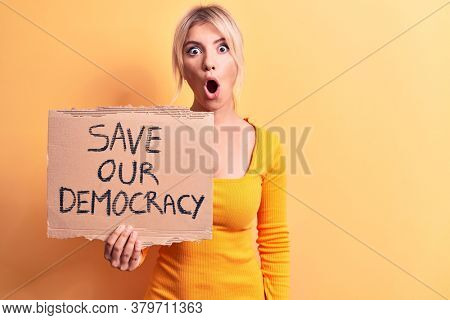 Young blonde woman asking for politics holding banner with save our democracy message scared and amazed with open mouth for surprise, disbelief face