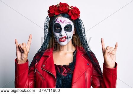 Woman wearing day of the dead costume doing rock and roll gesture with fingers clueless and confused expression. doubt concept.