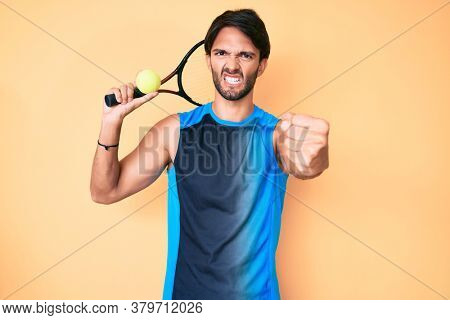 Handsome hispanic man playing tennis holding racket and ball annoyed and frustrated shouting with anger, yelling crazy with anger and hand raised