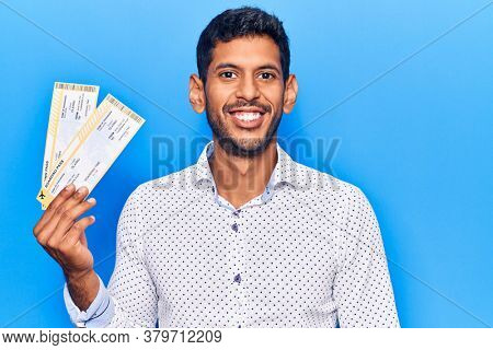 Young latin man holding boarding pass looking positive and happy standing and smiling with a confident smile showing teeth