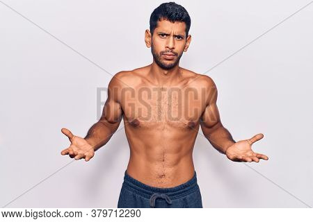 Young latin man standing shirtless clueless and confused expression with arms and hands raised. doubt concept.