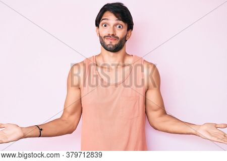 Handsome hispanic man wearing casual clothes clueless and confused expression with arms and hands raised. doubt concept.