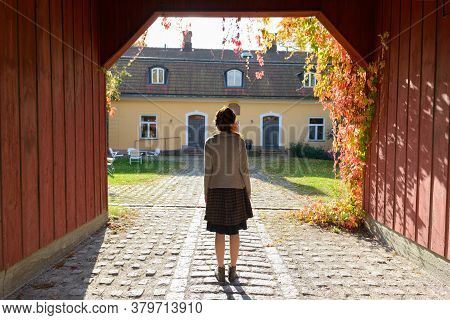 Rear View Of Young Woman Standing In Wooden Entrance Of Elegant Suburban House