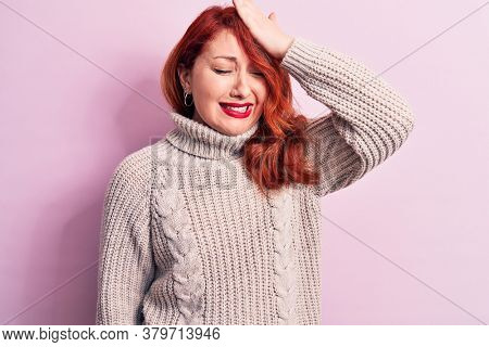 Young beautiful redhead woman wearing casual turtleneck sweater over pink background surprised with hand on head for mistake, remember error. Forgot, bad memory concept.