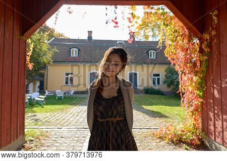 Young Happy Asian Woman Smiling In Wooden Entrance Of Elegant Suburban House