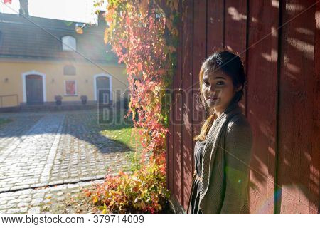 Young Happy Asian Woman Smiling Against Wooden Wall In Front Of Elegant Suburban House