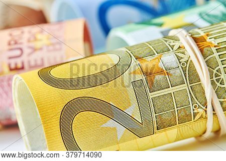 Two Hundred Euro Bill Rolled Up As A Tubule Lies On The Background Of Euro Bills. Two Hundred Euro B