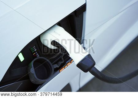 Charging A White Electric Car Close-up.altrernative Eco Energy Fuel.power Supply Connect To Electric