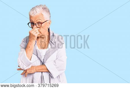 Senior beautiful woman with blue eyes and grey hair wearing casual clothes and glasses smelling something stinky and disgusting, intolerable smell, holding breath with fingers on nose. bad smell