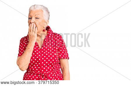 Senior beautiful woman with blue eyes and grey hair wearing a red summer dress bored yawning tired covering mouth with hand. restless and sleepiness.