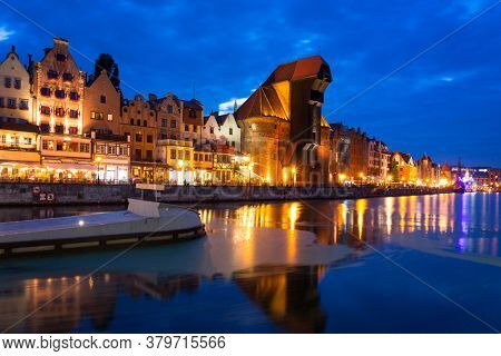 Amazing architecture of Gdansk old town over the Motlawa River at night.