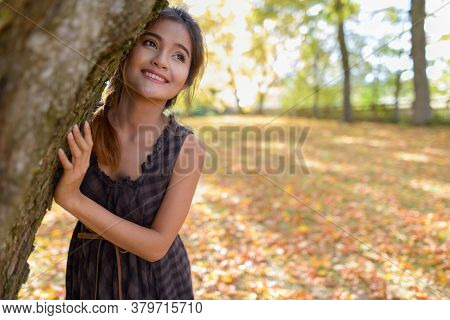 Young Happy Asian Woman Smiling While Looking Up Playfully Hiding Behind Tree