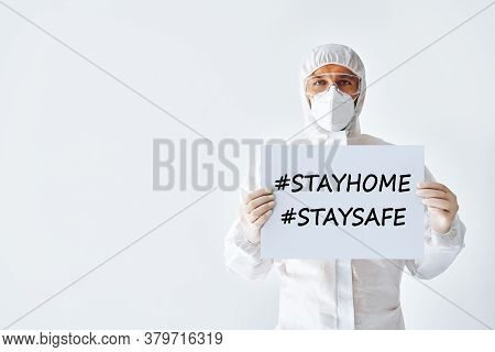 Doctor In Protective Medical Suit Showing Blank Placard Stay Home, Stay Safe On White Background