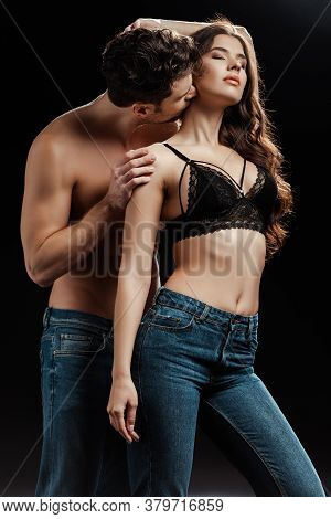 Shirtless Man Kissing Neck Of Sexy Woman In Bra And Jeans On Black