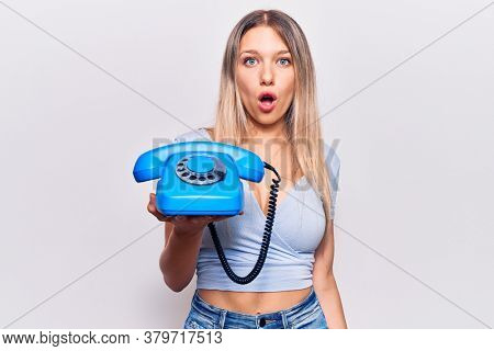 Young beautiful blonde girl holding vintage telephone scared and amazed with open mouth for surprise, disbelief face
