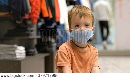 Kid Boy In A Protective Medical Mask Sits And Waits For Parents While Shopping In A Clothing Store E