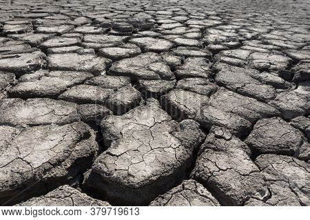Deep Cracks In The Ground Close-up. Wide Cracks In Dry Ground. Cracked Soil Caused By Dehydration.