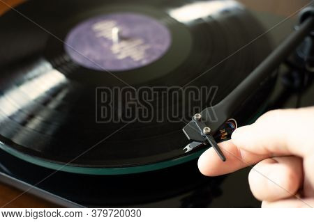 Vinyl Record Player With A Vinyl Disk. A Hand Lowers The Tonearm On The Vinyl Record.