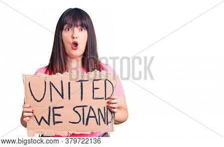 Young plus size woman holding united we stand banner scared and amazed with open mouth for surprise, disbelief face