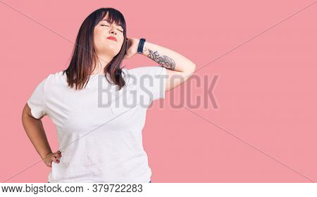 Young plus size woman wearing casual clothes suffering of neck ache injury, touching neck with hand, muscular pain