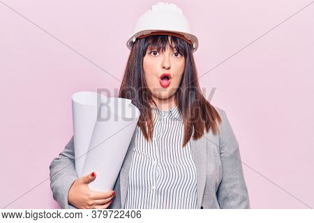Young plus size woman holding paper blueprints scared and amazed with open mouth for surprise, disbelief face