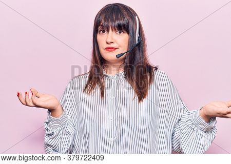 Young plus size woman wearing call center agent headset clueless and confused expression with arms and hands raised. doubt concept.