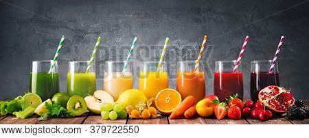 Panoramic food background with assortment of fresh fruits and vegetables juices in rainbow colors